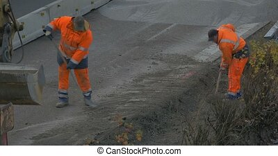 Two construction workers shoveling gravel on highway. flat...