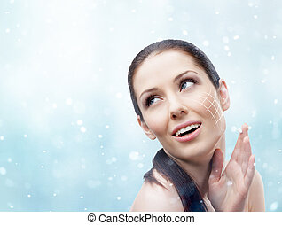 Woman applying face cream in winter - Woman applying face...