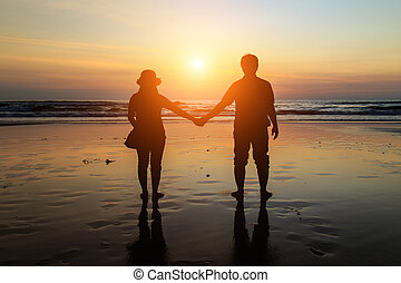 Silhouette of Thai Couple at the beach in sunset time