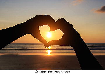 Silhouette of hands in heart symbol around the sun
