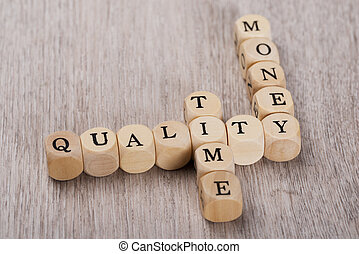 Quality; Time And Money Cubes Arranged On Table - Closeup of...