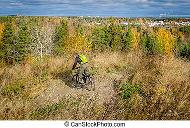 Autumn park downhill - Men riding bicycle downhill at...