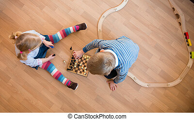 Brother and sister playing with chess. Photo from above