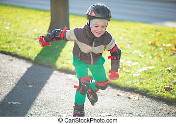 Happy little boy in sunny day on roller skates