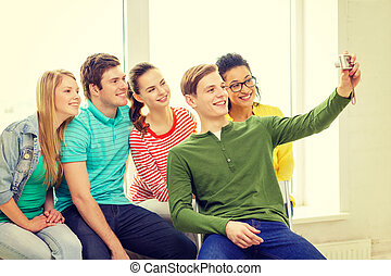 five smiling students taking picture with camera -...