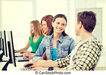 smiling students in computer class at school - education,...