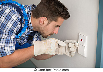 Man Repairing Light Switch At Home - Side view of young man...