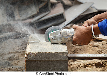 Hand holding angle grinder to cut the brick
