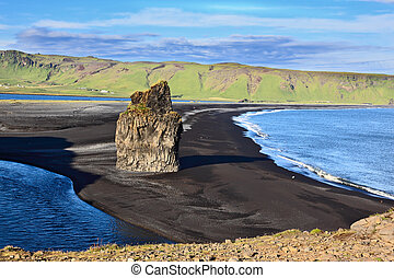 Cape Dirholaey in southern Iceland. On the beach with black...