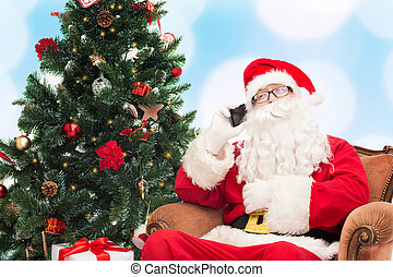 santa claus with smartphone and christmas tree - holidays,...