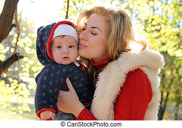 Mother kissing her baby girl in autumn park
