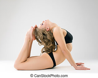 Flexible model posing while doing gymnastic ring in studio