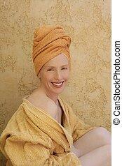 Beautiful woman with orange towel in head