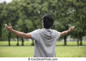 Asian man standing with arms raised outdoors. Concept about...