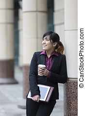 Asian business woman standing outside in modern city. -...