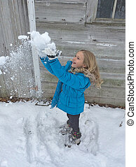 little girl playing in snow - Little blond girl playing in...