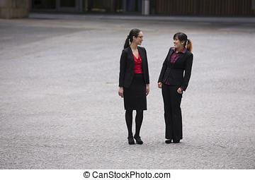 Two business women standing outside talking.