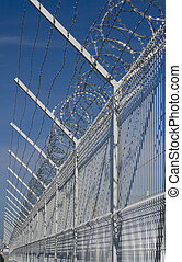 Barbed Wire - Fence with barbed wire on top on blue sky...