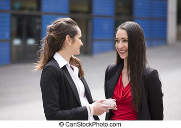 Two business women standing outside talking - Two business...
