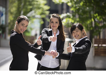 3 happy business woman with there thumbs up.