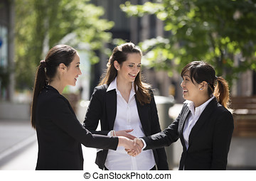 Female business colleagues shaking hands - Caucasian...