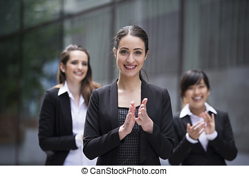 3 Business women clapping - Group portrait of three female...