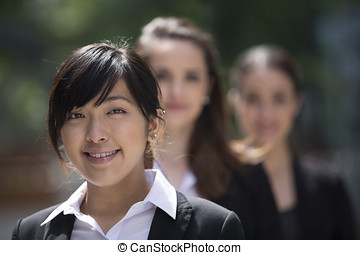 Portrait of three business women Focus is on caucasian woman...