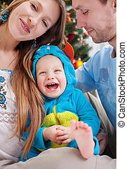 Young parents with baby son dressed in costume