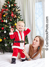 Mother playing with baby dressed in Santa costume