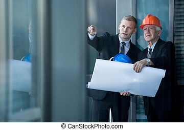Architects at work - Two experienced architects with helmets...