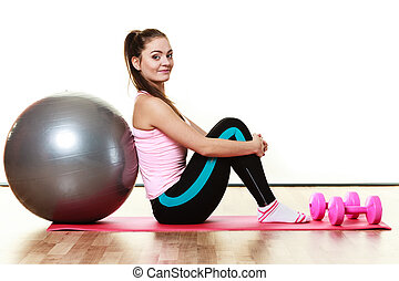 woman with gym ball and dumb bells isolated