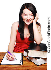 Smiling girl at desk writing on a notepad