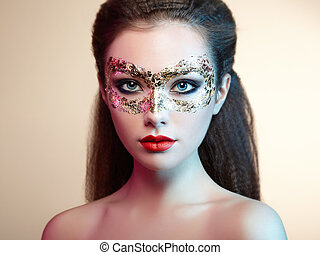Beautiful young woman in gold mysterious mask Perfect makeup...