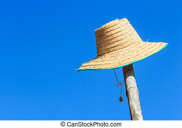 farmers hat was hanged on bamboo and blue sky in rural...