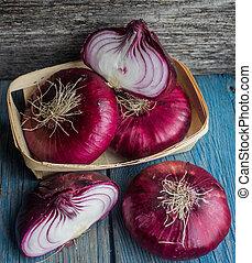 purple onion in a wicker basket on a wooden surface