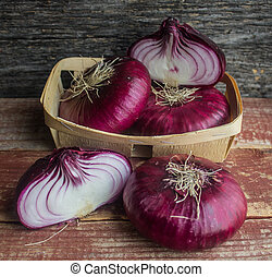 purple onion in a wicker basket on a wooden surface