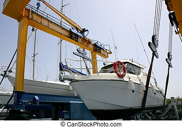 Dock crane elevating a fishing boat in Mediterranean marina