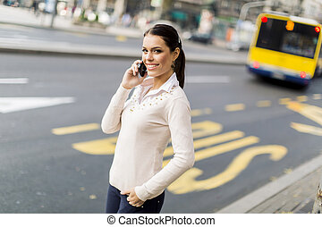 Young woman on the street - Pretty young woman talking on...