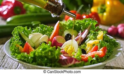 olive oil pouring over mixed salad - mixed salad and olive...