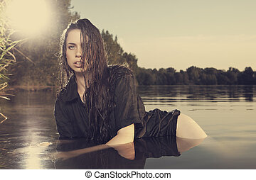 Pretty woman posing by the lake - Young female model posing...