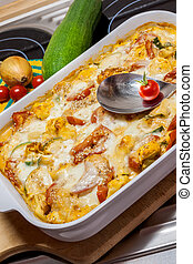 Tortellini Casserole with Tomatoes and Zucchini on a modern...