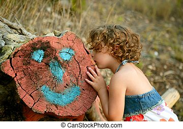 Girl kiss a cutted trunk with happy face draw, forest...