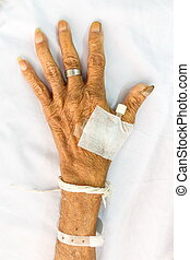hand of old patient with plug on bed in hospital