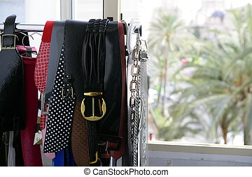 Rack of clothes with fashion accesories, belts - Rack of...