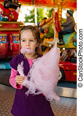 child with cotton candy - a little girl on a kirtag with...