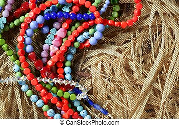 Color stones jewelry necklaces, straw background
