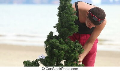 guy correct a Christmas tree on the beach - guy in shorts...