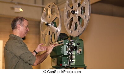 Film Technician Projecting Film - A technician projects a...