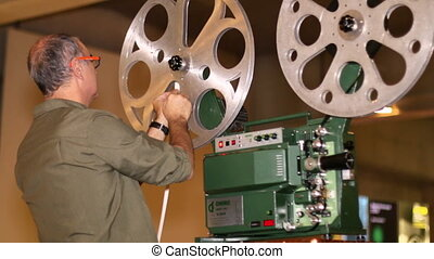 Film Technician Mounting 16mm Film - A technician mounts a...