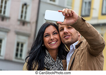 selfie a couple - a young couple making a self portrait with...